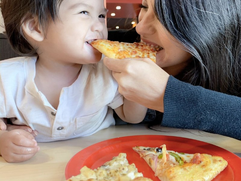 Image of Mother and daughter sharing a piece of Cici's pizza together